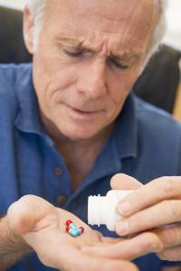 Pharmaceutical Malpractice Senior Man Pouring Pills Out Of Bottle